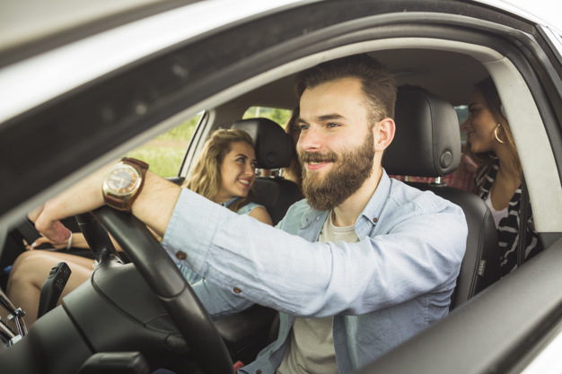handsome-man-with-his-friends-travelling-in-car_23-2147874597